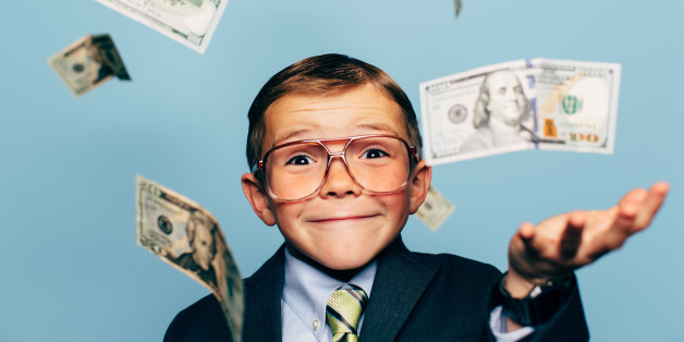 A young boy accountant wearing glasses catches U.S. currency while more falls from above. He is smiling and ready to do your taxes for the IRS and make your tax refund bigger.