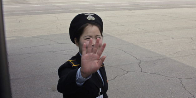 A ground staff of North Korean airliner Air Koryo thrusts a hand in front of her face at the airport in North Korean capital of Pyongyang October 12, 2010. REUTERS/Petar Kujundzic  (NORTH KOREA - Tags: POLITICS TRANSPORT)
