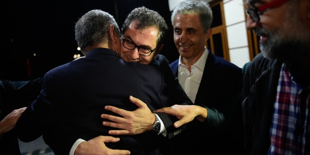 Turkish cartoonist Musa Kart (L) embraces Kadri Gursel (2nd L) as the representative of the international rights group Reporters Without Borders (RSF) in Turkey, Erol Onderoglu (R), holds his hand after the Gursel's release from Silivri prison on September 26, 2017 in Istanbul, following a Turkish court order to free the columnist and editorial director of Turkey's opposition newspaper Cumhuriyet.