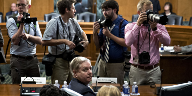 Senator Lindsey Graham, a Republican from South Carolina, bottom center, stays seated during a disruption in a Senate Finance Committee hearing to consider the Graham-Cassidy-Heller-Johnson proposal in Washington, D.C., U.S., on Monday, Sept. 25, 2017. Senators sponsoring a last-ditch Obamacare repeal bill raced to save it from near-certain death Sunday, circulating a new version aimed at winning over several GOP holdouts. Photographer: Andrew Harrer/Bloomberg via Getty Images