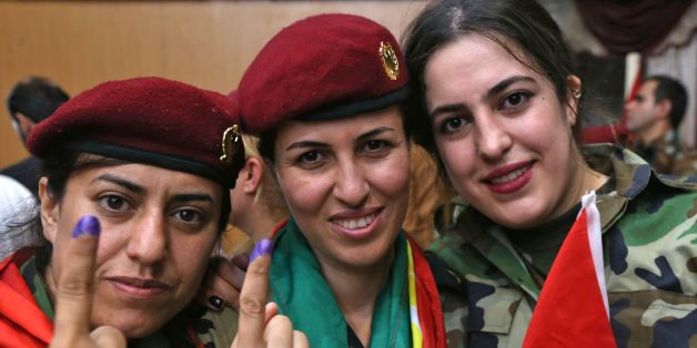Female members of a Kurdish Peshmerga battalion show their ink-stained fingers after casting their vote in the Kurdish independence referendum in Arbil, on September 25, 2017. Iraqi Kurds voted in an independence referendum in defiance of Baghdad which has warned of 'measures' to defend Iraq's unity and threatened to deprive their region of lifeline oil revenues. / AFP PHOTO / SAFIN HAMED        (Photo credit should read SAFIN HAMED/AFP/Getty Images)
