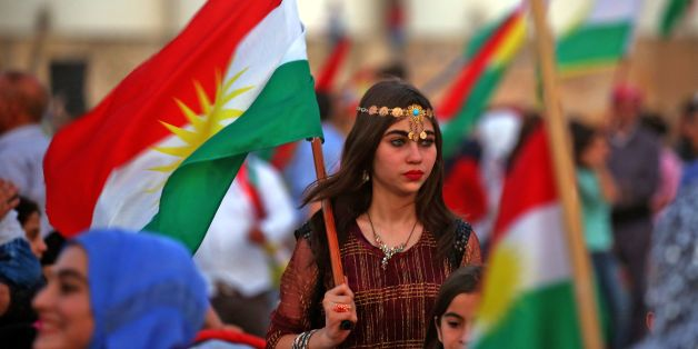 Syrian Kurds wave the Kurdish flag in celebration, in the northeastern Syrian city of Qamishli on September 26, 2017, in support of the independence referendum in Iraq's autonomous northern Kurdish region. / AFP PHOTO / Delil souleiman        (Photo credit should read DELIL SOULEIMAN/AFP/Getty Images)