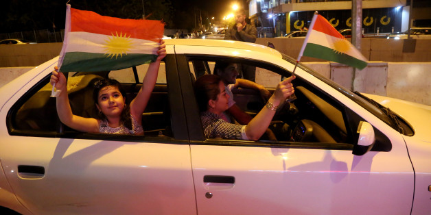 SULAYMANIYAH, IRAQ - 2017/09/25: A Kurdish family is seen inside their car while holding Kurdish flags and celebrating the referendum during the night. September 25, 2017 is a historic day for Kurdish people around the world as many Kurdish took part in a landmark vote on independence for Iraq's Kurdistan region. Votes are currently still being counted, with an expected victory for YES. The referendum runned off quietly in the three provinces that make up the region, and in places controlled by Kurdish forces. The Kurdish Rudaw website published recently that more than 90% have voted for independence. (Photo by Rahman Hassani/SOPA Images/LightRocket via Getty Images)
