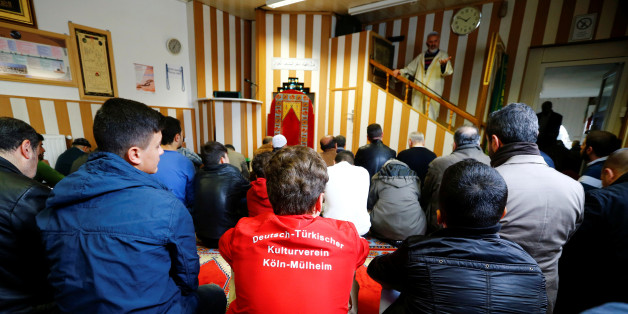"Young Muslims listen to a Turkish imam during Friday prayers at the Turkish Kuba Camii mosque located near a hotel housing refugees in Cologne's district of Kalk, Germany, October 14, 2016. Picture taken October 14, 2016. Youth in foreground wears a shirt reading, ""German-Turkish culture club Cologne-Muehlheim"". Picture taken October 14, 2016. To match Insight EUROPE-MIGRANTS/GERMANY-MOSQUES   REUTERS/Wolfgang Rattay"