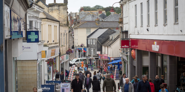 REDRUTH, UNITED KINGDOM - JULY 26:  People walk along the main street in Redruth on July 26, 2017 in Cornwall, England.  Figures released by Eurostat in 2014 named the British county of Cornwall as one of Europe's top ten poverty areas falling behind Poland, Lithuania and Hungary. Average wages were £14,300 compared with the UK national figure of £23,300 and £20,750 across Europe. UK government statistics show almost a quarter of people living in the Camborne, Pool and Redruth (CPR) area of Cornwall are in one of the most deprived areas of England with the highest level of childhood obesity, almost a quarter of children aged under 16 living in poverty and the lowest life expectancy.  The area, which has long suffered from severe industrial decline with the demise of the copper and tin mining industries, has not shared in the wealth created in nearby tourist havens such as Newquay, Padstow and St Ives.  Cornwall is the only UK county to have previously received emergency funding from the European Union (EU) and was one of the major beneficiaries of the UK's membership of the EU due to the large amount of funding made available through the EUs Objective One and Convergence programmes.  Despite this voters overwhelmingly backed the campaign to leave the European Union in the June 2016 referendum. (Photo by Matt Cardy/Getty Images)