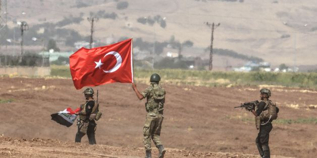 Soldiers holding Turkish and Iraqi flags walk during a joint military exercise near the Turkish-Iraqi border in Sirnak in Silopi district on September 26, 2017. 