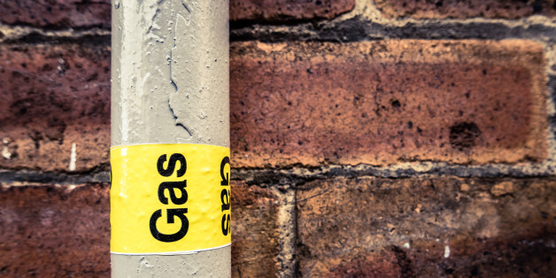 Detail Of A Residential Gas Pipe Against A Red Brick Wall