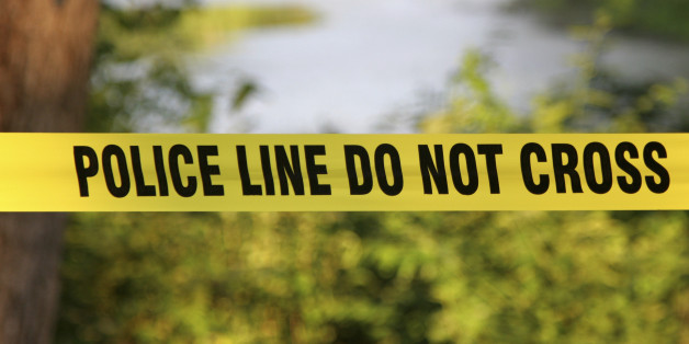 Police Do Not Cross aa yellow plastic tape in a forest.