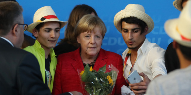 SCHWERIN, GERMANY - SEPTEMBER 19:  German Chancellor and Christian Democrat (CDU) Angela Merkel poses for a photo with Syrian refugees after she spoke at an election campaign stop on September 19, 2017 in Schwerin, Germany. Merkel is seeking a fourth term in German federal elections scheduled for September 24 and currently has a double-digit lead over her main rival, German Social Democrat (SPD) Martin Schulz.  (Photo by Sean Gallup/Getty Images)