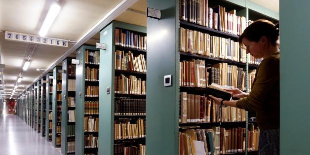 "A woman consults a book in the library of the university KU Leuven ""Katholieke Universiteit Leuven"" in Leuven, Belgium, June 8, 2016. REUTERS/Francois Lenoir"