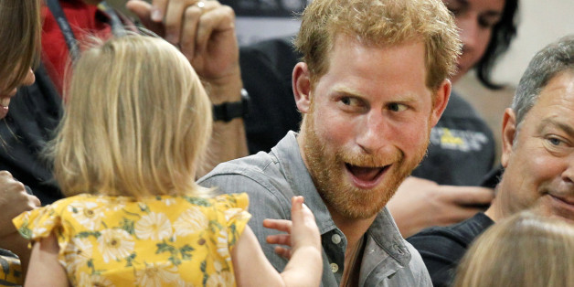 Britain's Prince Harry, patron of the Invictus Games Foundation, shares popcorn with a child while attending the Sitting Volleyball competition at the games in Toronto, Ontario, Canada, September 27, 2017.  REUTERS/Fred Thornhill