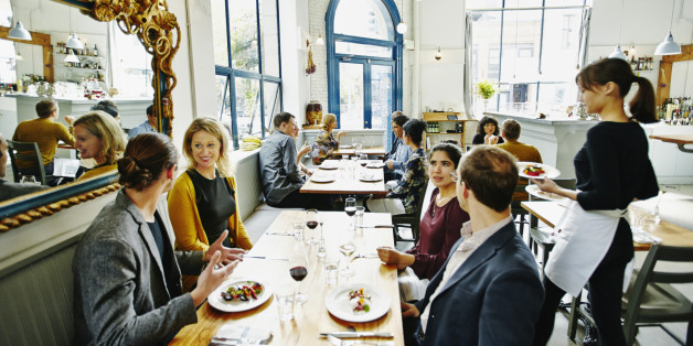 Waitress delivering food to group of friends dining together at table in restaurant