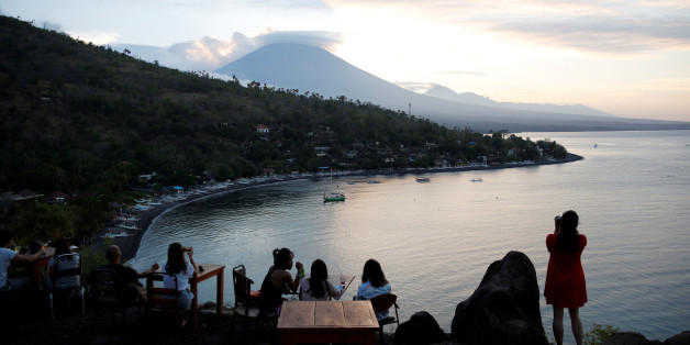 Tourists have a drink while watching the sunset behind Mount Agung, a volcano on the highest alert level, in Amed on the resort island of Bali, Indonesia September 25, 2017. REUTERS/Darren Whiteside