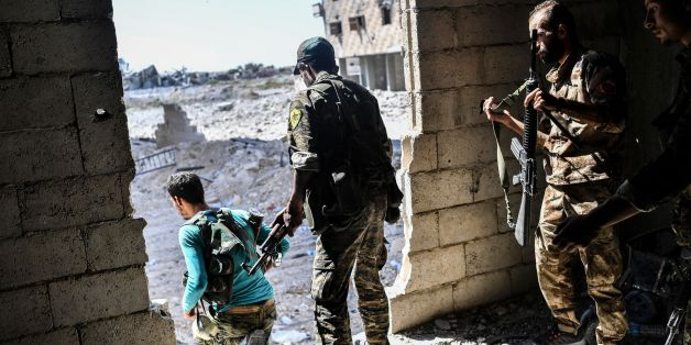 Members of the Syrian Democratic Forces hold a position as they advance to take the central hospital of Raqa on the weastern frontline of the city on September 28, 2017. Syrian fighters backed by US special forces are battling to clear the last remaining Islamic State group jihadists holed up in their crumbling stronghold of Raqa. / AFP PHOTO / BULENT KILIC        (Photo credit should read BULENT KILIC/AFP/Getty Images)