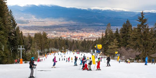Bansko, Bulgaria - February 11, 2016:  Skiers on the slope , ski lift, mountains view and Bansko town panorama