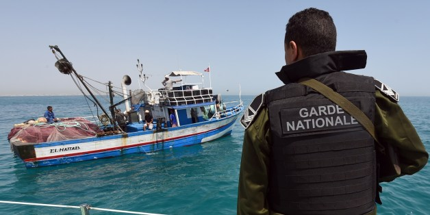 A member of the Tunisia's national guard stops a fishing boat in the sea bordering Tunisia and Libya as they check vessels for illegal migrants trying to reach Europe on May 5, 2015 off the coast of Tunisia's southeast port of Zarzis. AFP PHOTO/FETHI BELAID         (Photo credit should read FETHI BELAID/AFP/Getty Images)
