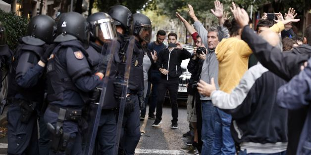 People raise their arms in front of Spanish police after the seizure of ballot boxes in a polling station in Barcelona, on October 1, 2017, on the day of a referendum on independence for Catalonia banned by Madrid.More than 5.3 million Catalans are called today to vote in a referendum on independence, surrounded by uncertainty over the intention of Spanish institutions to prevent this plebiscite banned by justice. / AFP PHOTO / PAU BARRENA        (Photo credit should read PAU BARRENA/AFP/Getty I