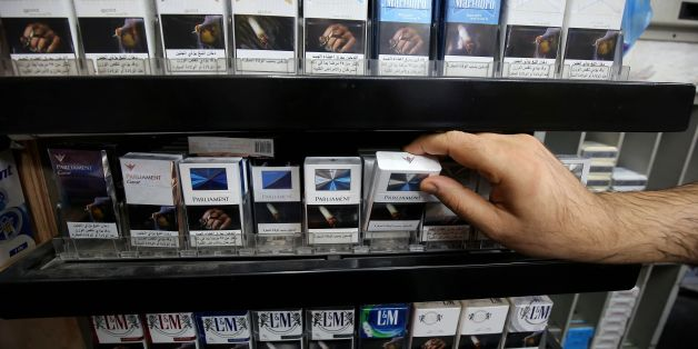 A picture taken on September 29, 2017 shows a close up shot of a vendor organizing cigarette boxes at a shop in Kuwait City.On October 1, 2017, the United Arab Emirates will double the price of tobacco and increase soft drink prices by 50 percent, ahead of a more general tax on goods and services on January 1 next year. It is but one of the six Gulf Cooperation Council states -- along with Saudi Arabia, Bahrain, Kuwait, Oman and Qatar -- to introduce the five-percent VAT next year as they seek t