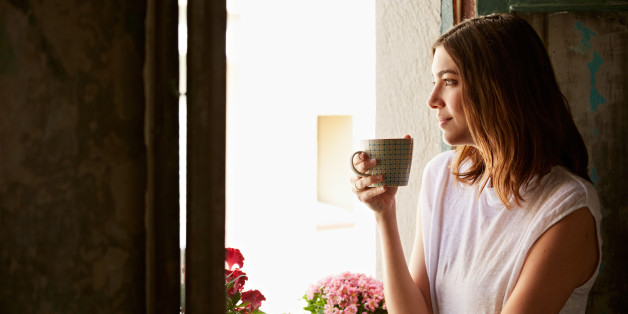 Shot of a young woman drinking a cup of coffee while looking out of a window