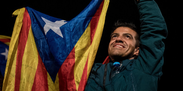 BARCELONA, SPAIN - OCTOBER 01:  People wave Catalan flags as they dance and sing after listening to Catalan President Carles Puigdemont speak via a televised press conference as they await the result of the Indepenence Referendum at the Placa de Catalunya  on October 1, 2017 in Barcelona, Spain. More than five million eligible Catalan voters are estimated to visit 2,315 polling stations today for Catalonia's referendum on independence from Spain. The Spanish government in Madrid has declared the