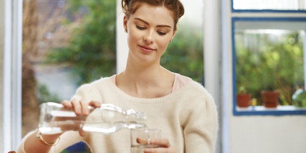 Shot of a young woman pouring a glass of water at home