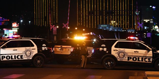 TOPSHOT - Police form a perimeter around the road leading to the Mandalay Hotel (background) after a gunman killed at least 50 people and wounded more than 200 others when he opened fire on a country music concert in Las Vegas, Nevada on October 2, 2017. Police said the gunman, a 64-year-old local resident named as Stephen Paddock, had been killed after a SWAT team responded to reports of multiple gunfire from the 32nd floor of the Mandalay Bay, a hotel-casino next to the concert venue. / AFP PH