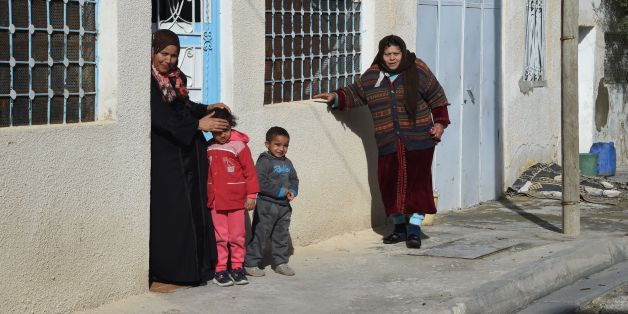 Neighbours of the family of of 24-year-old Anis Amri, the prime suspect in Berlin's deadly truck attack, watch as the media gather in front of Amri's house in the town of Oueslatia, in Tunisia's region of Kairouan on December 22, 2016.