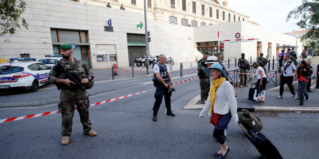 Travellers walk past French police and soldiers who secure a street near the Saint-Charles train station  (Rear) after French soldiers shot and killed a man who stabbed two women to death at the main train station in Marseille, France, October 1, 2017.  REUTERS/Jean-Paul Pelissier