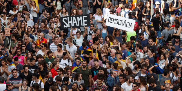 People hold up placards during a demonstration two days after the banned independence referendum in Barcelona, Spain, October 3, 2017. REUTERS/Yves Herman