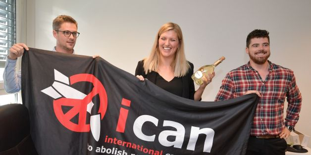 (From L) Nuclear disarmament group ICAN coordinator Daniel Hogstan, executive director Beatrice Fihn and her husband Will Fihn Ramsay pose with a banner bearing the group's logo after ICAN won the Nobel Peace Prize for its decade-long campaign to rid the world of the atomic bomb as nuclear-fuelled crises swirl over North Korea and Iran, on October 6, 2017 in Geneva.