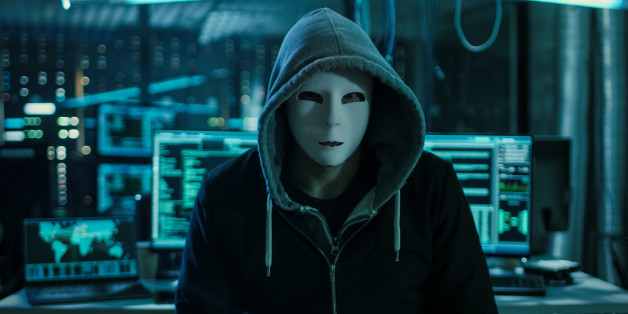 Dangerous Internationally Wanted Hacker with Covered Face Looking into the Camera. In the Background His Operating Room with Multiple Displays and Cables.
