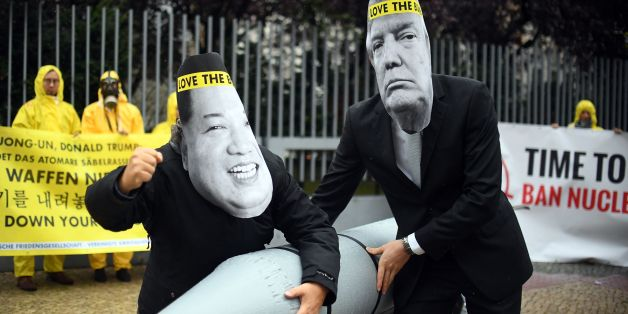 Picture taken on September 13, 2017 shows activists of the International campaign to abolish Nuclear Weapons (ICAN) wearing masks of US President Donald Trump (R) and North Korea's leader Kim Jong-un as they demonstrate in front of the US embassy in Berlin.The world's nuclear powers must begin 'serious negotiations' aimed at disarmament, the Nobel committee said on October 6, 2017 as it awarded its prestigious Peace Prize to non-proliferation pressure group ICAN. / AFP PHOTO / dpa / Britta Peder