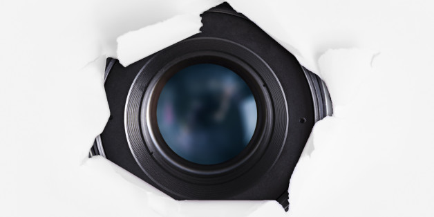 Camera lens hiding behind the paper wall. Spy concept.