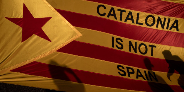 BARCELONA, SPAIN - OCTOBER 03:  Protesters shadows are seen on a Catalan flag as thousands of citizens gather in Plaza Universitat during a regional general strike to protest against the violence that marred Sunday's referendum vote on October 3, 2017 in Barcelona, Spain. According to the Catalonia's government more than two million people voted on Sunday in the referendum of Catalonia, which the Government in Madrid had declared illegal and undemocratic. Officials said that 90% of votes cast we