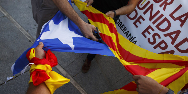 MADRID, SPAIN - OCTOBER 07:  Demonstrators cut off the star from a Catalan Pro-Independence flag known as 'Estelada' during a protest against the independence of Catalonia under the slogan 'For the unity of Spain' called by far right wing party Falange Espanola de la Jons at Salvador Dali Square on October 7, 2017 in Madrid, Spain. Tension between the central government and the Catalan region have increased after last weekend's independence referendum. The Spanish government suspended the Catala