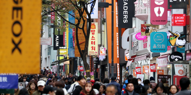 People walk past stores at the Myeongdong shopping district in Seoul, South Korea, on Monday, Oct. 31, 2016. As South Korean President Park Geun-hye's popularity plummets, members of her own party are publicly demanding action to staunch the bleeding from an influence-peddling scandal. Photographer: SeongJoon Cho/Bloomberg via Getty Images