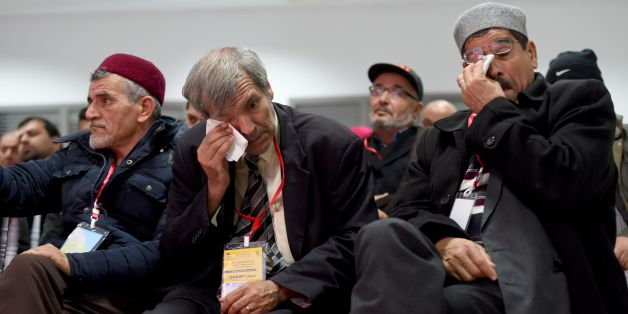 Men wipe their tears as relatives of abuse victims watch a live broadcast of testimonials by abuse victims before the Truth and Dignity Commission in Tunis on December 16, 2016. 