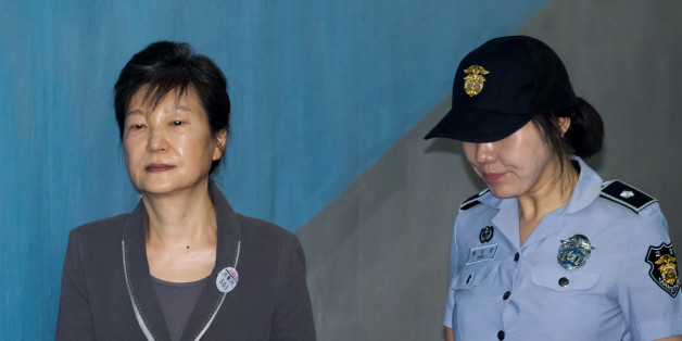Park Geun-hye, former president of South Korea, left, is escorted by a prison officer as she arrives at the Seoul Central District Court in Seoul, South Korea, on Thursday, July 27, 2017. Jay Y. Lee, the de facto head of theSamsung conglomerate, is on trial for bribery and embezzlement, part of a series of scandals that led in March to the ouster ofPark. Photographer: SeongJoon Cho/Bloomberg via Getty Images