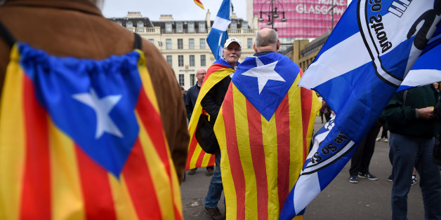 Demonstrators display the Catalan Flag, the Senyera (L) and the Flag of Scotland, the Saltire (R) painted on their faces during a protest to show solidarity with Catalonia, in central Glasgow on October 9, 2017.The Scottish National Party on October 10, 2017 urged the Spanish government to 'respect the overwhelming 'si' vote' in the Catalan independence referendum in a resolution at its annual conference. / AFP PHOTO / ANDY BUCHANAN        (Photo credit should read ANDY BUCHANAN/AFP/Getty Images