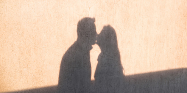 The shadow on the wall of a young loving couple kissing each other and enjoy the tenderness. Happy and loving couple for Valentine's Day.