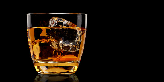 Whiskey in glass on black background