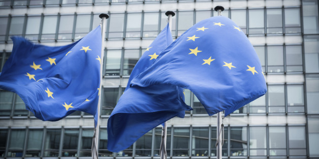 'European flags in front of the European Commission headquarters in Brussels, Belgium. ( Motion Blurred on flags)'
