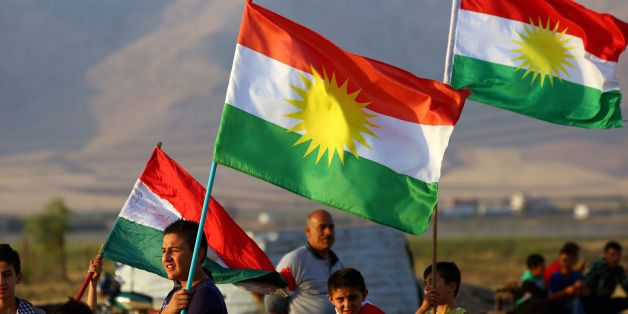 Syrian Kurds wave the Kurdish flag, in the northeastern Syrian city of Qamishli on September 27, 2017, during a gathering in support of the independence referendum in Iraq's autonomous northern Kurdish region. Iraq's Kurds announced a massive 'yes' vote for independence following a referendum that has incensed Baghdad and sparked international concern. / AFP PHOTO / DELIL SOULEIMAN        (Photo credit should read DELIL SOULEIMAN/AFP/Getty Images)