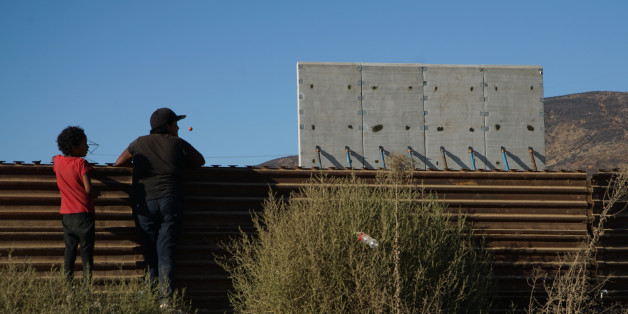 TIJUANA, MEXICO - OCTOBER 5:  People watch  prototype sections of a border wall between Mexico and the United States under construction on October 5, 2017 in Tijuana, Mexico. Prototypes of the border wall propopsed by President Donald Trump are being built just north of the U.S.- Mexico border, where competitors who are hoping to gain approval to build the wall have until the first of next month to complete their work. (Photo by Sandy Huffaker/Getty Images)