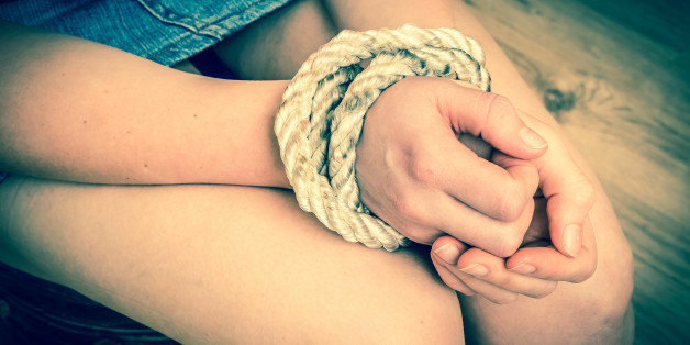 Kidnapped woman tied with rope - abuse and violence concept