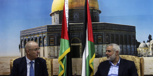 Senior Hamas leader Ismail Haniyeh (R) speaks with Palestinian Prime Minister Rami Hamdallah at Haniyeh's house in Gaza City October 9, 2014. Hamdallah arrived in the Hamas-dominated Gaza Strip on Thursday and convened the first meeting of a unity government there since a brief civil war in 2007 between Hamas and forces loyal to the Fatah party.     REUTERS/Ibraheem Abu Mustafa (GAZA - Tags: POLITICS CIVIL UNREST)