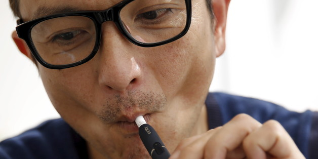 """A customer tries a Philip Morris' """"iQOS"""" smokeless tobacco e-cigarette at an iQOS store in Tokyo, Japan, March 3, 2016.   REUTERS/Toru Hanai"""