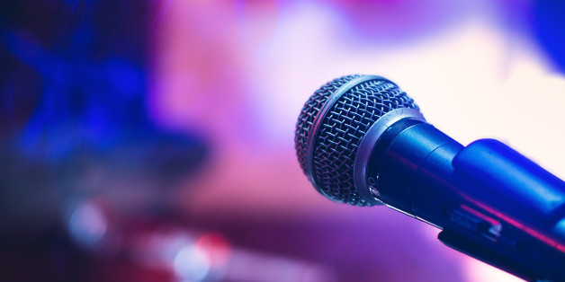 Microphone on the stage on violet background.