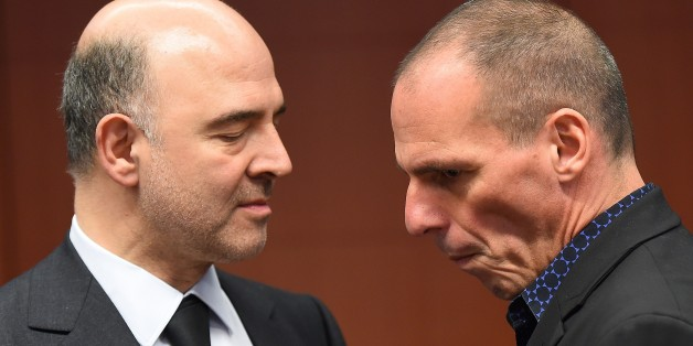 Greece's Finance Minister Yanis Varoufakis (R) speaks with European Commissioner for Economic and Financial Affairs, Taxation and Customs Pierre Moscovici during a Eurogroup finance ministers meeting at the European Council in Brussels, March 9, 2015. AFP PHOTO / EMMANUEL DUNAND        (Photo credit should read EMMANUEL DUNAND/AFP/Getty Images)