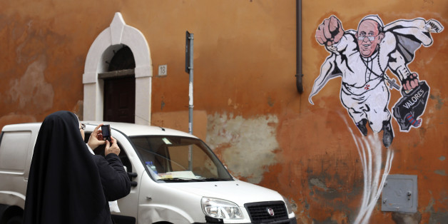 A nun takes a picture of a large drawing of Pope Francis depicting him as a superhero on a wall near the Vatican January 29, 2014. The Argentinian Pope is shown taking off into air with his right fist clenched in a classic Superman style.  REUTERS/Alessandro Bianchi (ITALY - Tags: RELIGION SOCIETY)
